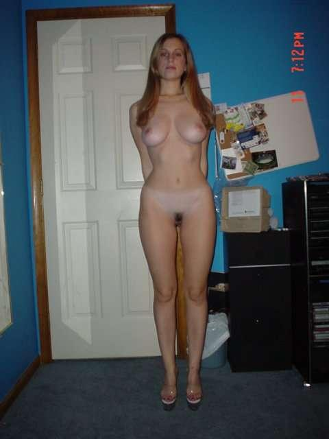 Nude redhead takes a photo