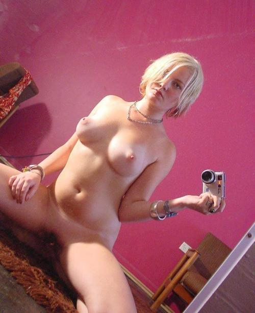 Naked blonde reveals her shaved twat