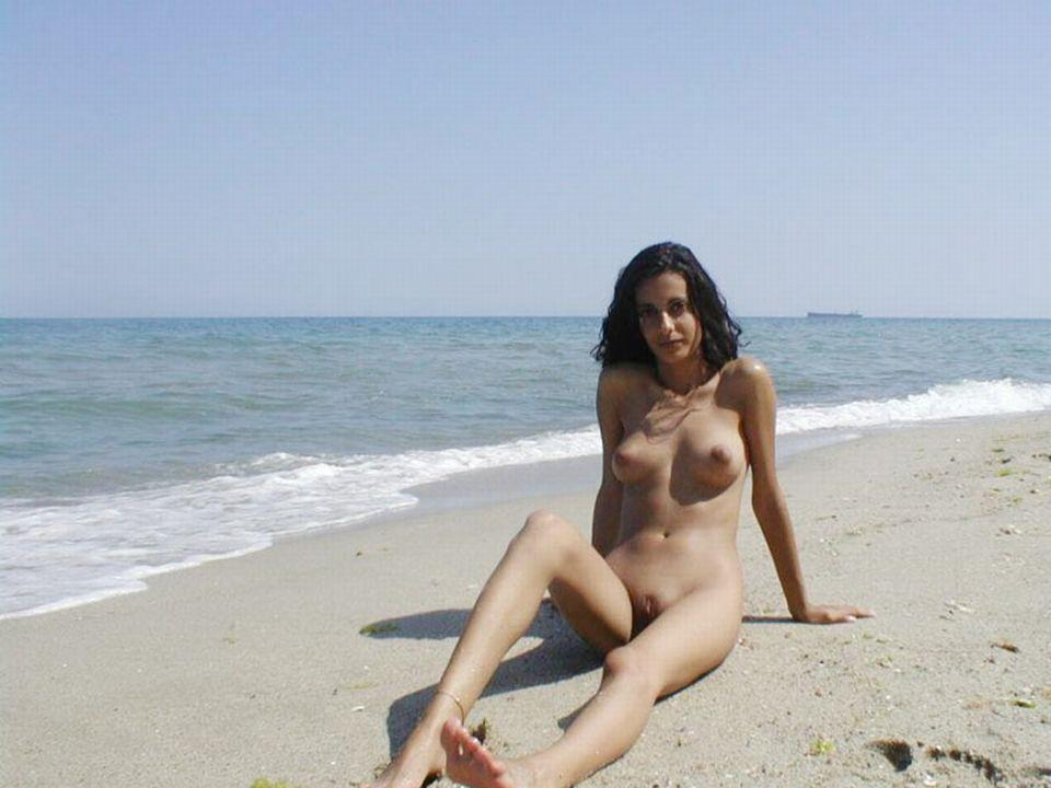 Resting her naked perfect body on the beach