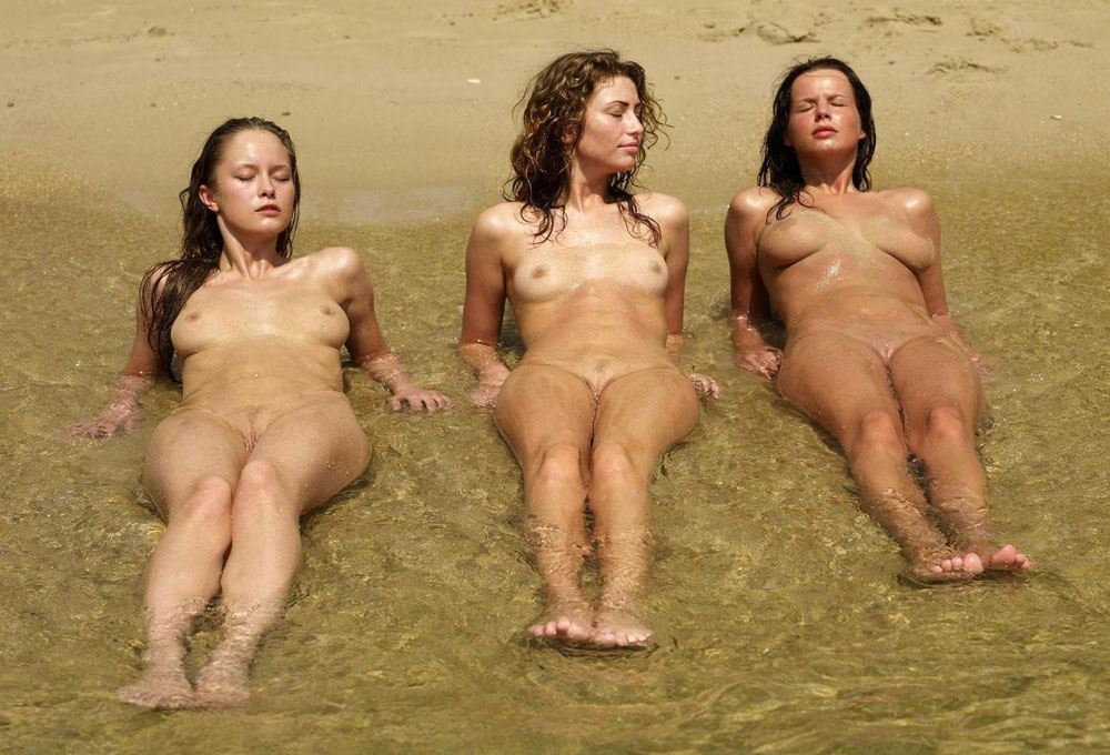 Three nude mermaids laying in the water