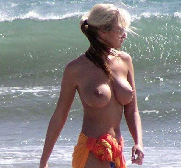 Buxom beauty flaunts perfect breasts on the beach